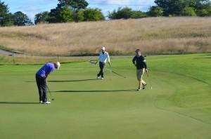 Patrick Sjöland holder flaget, og Morten Ørum Madsen kigger på, mens sidste års ECCO Tour vinder, Jesper Kennegård rydder op på hul 7 på Himmerland Golf & Spa Resort